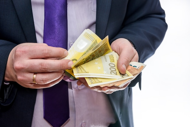 Mężczyzna w garniturze liczenia banknotów euro z bliska