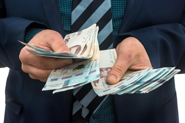 Mężczyzna w garniturze liczy zyski. męskie ręce konwertują hrywny. 1000 nowych banknotów, ukraińskie pieniądze