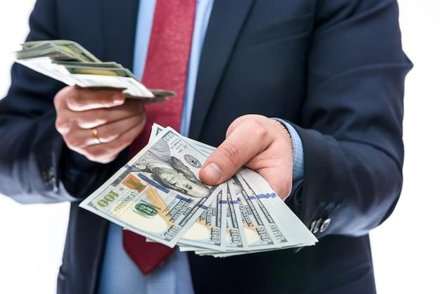 Mężczyzna w garniturze na białym tle pokazujący banknoty dolarowe