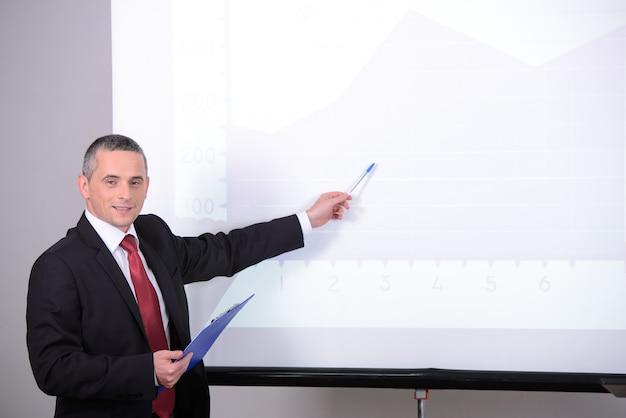 Mężczyzna w garniturze na spotkaniu biznesowym coś wyjaśnia.