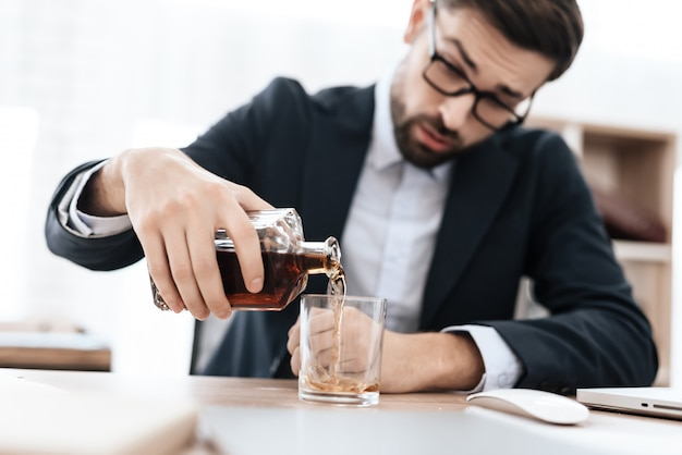 Mężczyzna w garniturze nalewa sobie alkohol w biurze