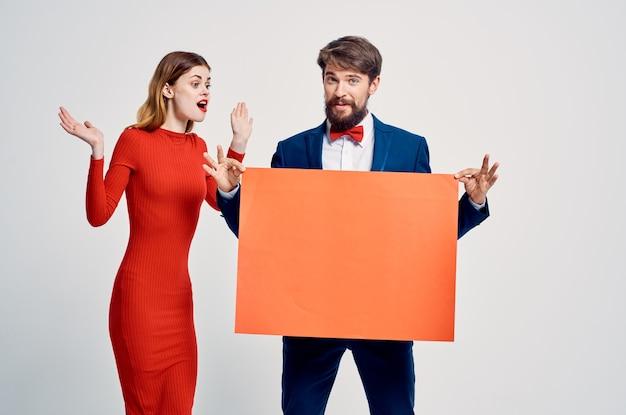 Mężczyzna w garniturze obok kobiety w czerwonej sukience miejsce na kopię prezentacji reklamowej