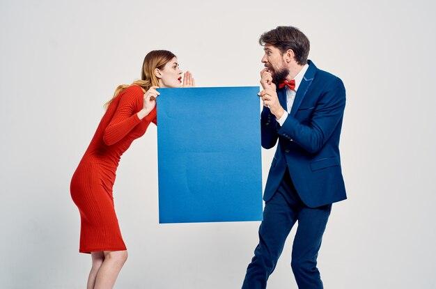 Mężczyzna w garniturze obok kobiety w czerwonej sukience niebieski plakat reklamowy miejsce na kopię