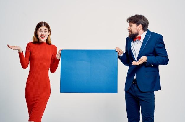 Mężczyzna w garniturze obok kobiety w czerwonej sukience niebieski plakat reklamowy prezentacji makiety