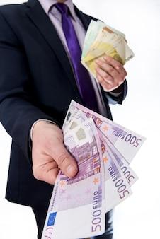 Mężczyzna w garniturze oferując banknoty euro na białym tle