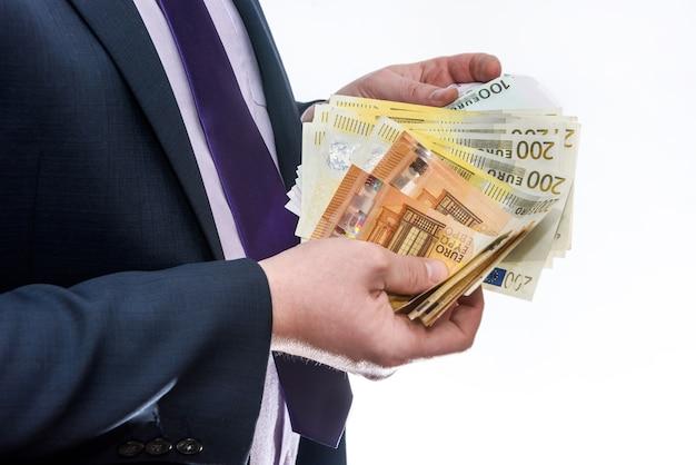 Mężczyzna w garniturze oferujący banknoty euro z bliska