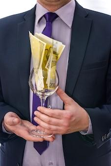 Mężczyzna w garniturze oferujący szkło z banknotami euro