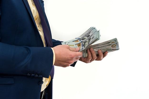 Mężczyzna w garniturze oferuje łapówkę za produkt lub usługę. biznesmen trzyma dolary i daje. korupcja lub wynagrodzenie.