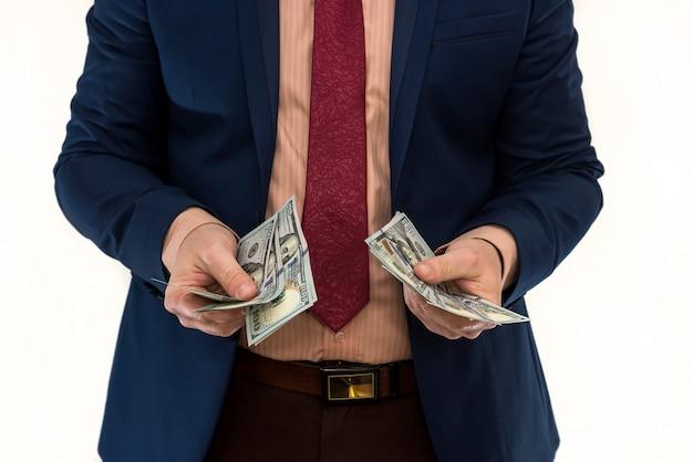 Mężczyzna w garniturze oferuje łapówkę za produkt lub usługę. biznesmen trzyma i daje dolary. korupcja lub wynagrodzenie.
