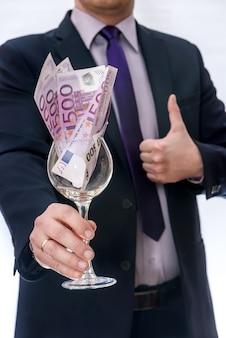 Mężczyzna w garniturze oferuje szkło z banknotami euro