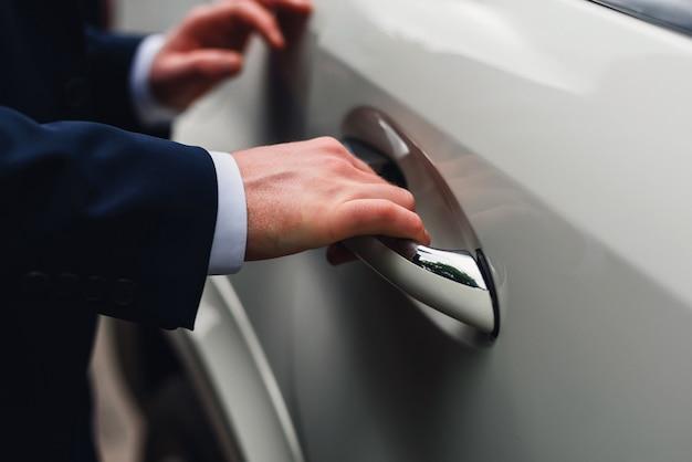 Mężczyzna w garniturze otwiera drzwi samochodu