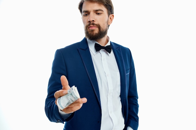 Mężczyzna w garniturze pieniądze w dłoni jasnym tle