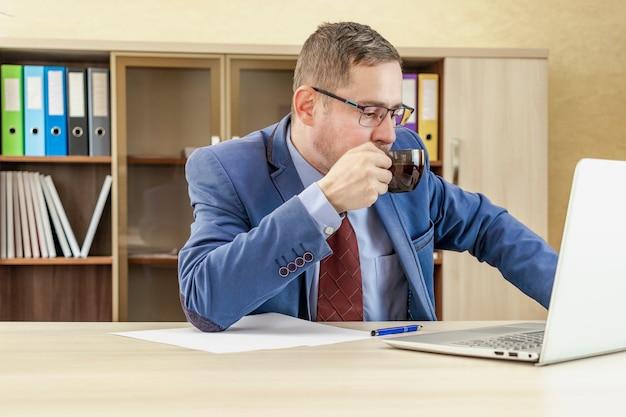 Mężczyzna w garniturze pije herbatę z kubka patrząc na ekran laptopa rano