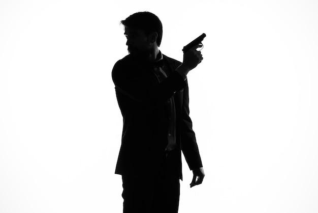 Mężczyzna w garniturze pistolet w rękach emocji sylwetka światło tło