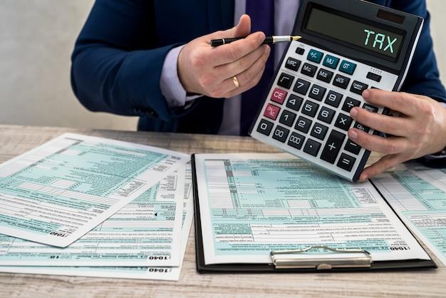 Mężczyzna W Garniturze Pisze W Urzędzie Formularz Podatkowy 1040. Męskie Dłonie Wypełnić Na Papierze Z Kalkulatorem W Miejscu Pracy. Koncepcja Rachunkowości Premium Zdjęcia