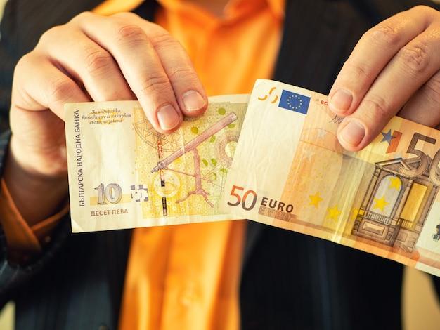 Mężczyzna w garniturze pokazuje pieniądze w bułgarskich lewach i euro