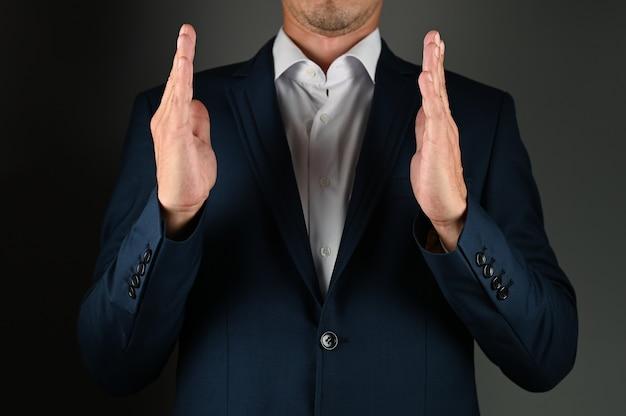 Mężczyzna w garniturze pokazuje rozmiar rękami. wysokiej jakości zdjęcie