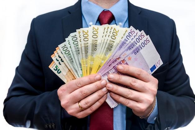 Mężczyzna w garniturze posiada nominały euro