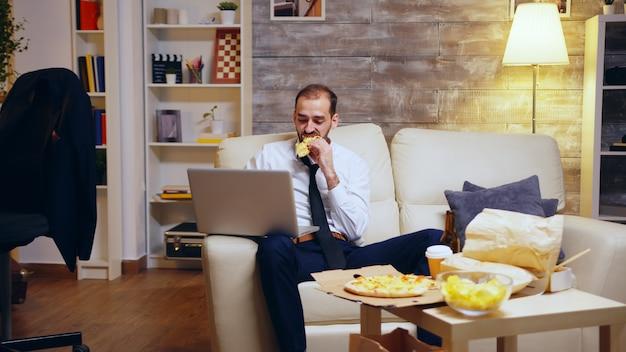 Mężczyzna w garniturze pracuje do późna w nocy na laptopie przed telewizorem, jedząc niezdrowe jedzenie.