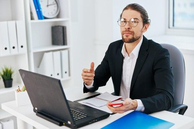 Mężczyzna w garniturze pracuje w biurze przed laptopem?