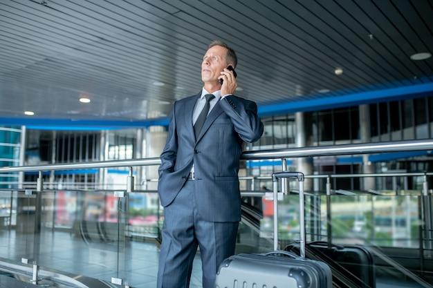 Mężczyzna w garniturze rozmawia na smartfonie na lotnisku