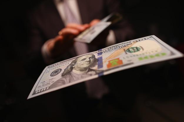 Mężczyzna w garniturze ściółki pieniądze, dolary zbliżenie