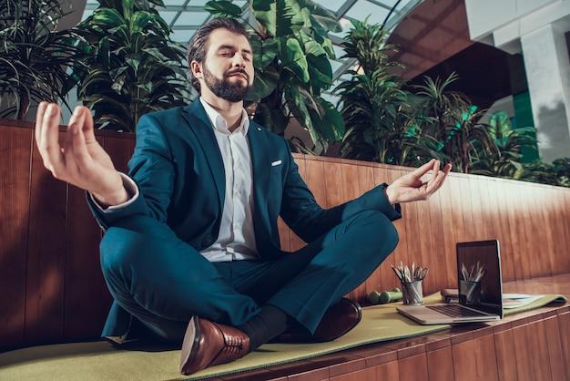 Mężczyzna w garniturze siedzi i medytuje.
