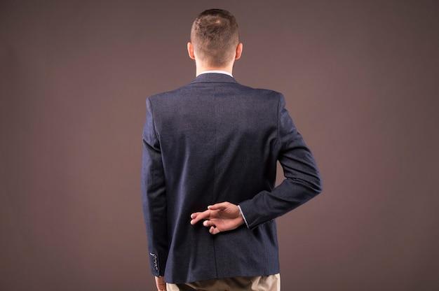 Mężczyzna w garniturze skrzyżował palce za plecami