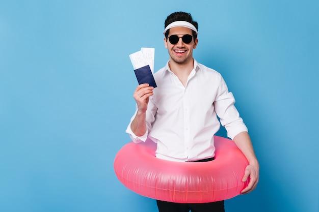 Mężczyzna w garniturze stawia na nadmuchiwane koło i uśmiecha się. facet w okularach przeciwsłonecznych i czapce ma paszport i bilety.