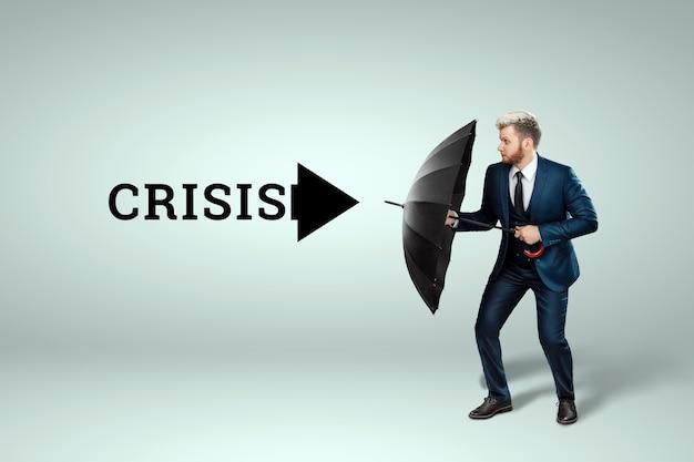 Mężczyzna w garniturze stoi z parasolem w rękach i chroni się przed kryzysem