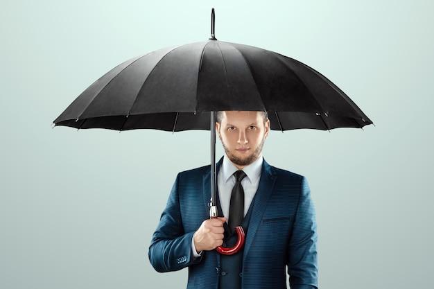 Mężczyzna w garniturze stoi z parasolem w rękach na jasnym tle