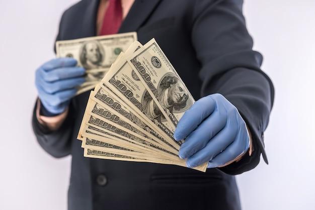 Mężczyzna w garniturze trzyma pieniądze 100 dolarów rachunki w rękawicach medycznych dla bezpieczeństwa. kryzys koronawirusowy. covid-19