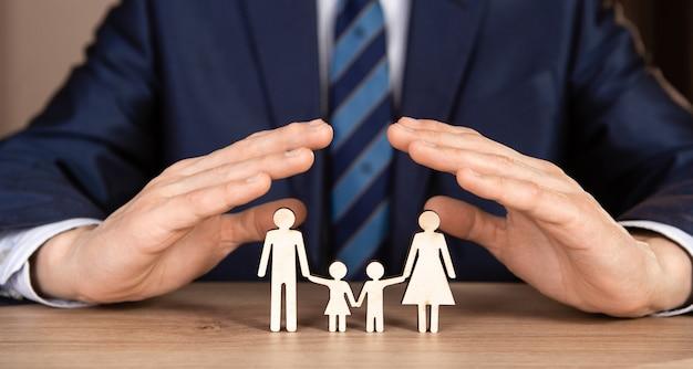 Mężczyzna w garniturze trzyma ręce w kształcie domu nad rodziną. koncepcja ubezpieczenia.