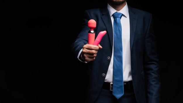 Mężczyzna w garniturze trzyma różowe wibratory