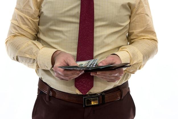 Mężczyzna w garniturze trzyma wiele dolarów w dolarach