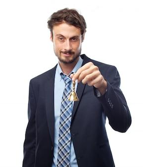 Mężczyzna w garniturze trzyma złoty dzwon