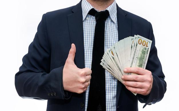 Mężczyzna w garniturze, trzymając banknoty dolara na białym tle na białej ścianie