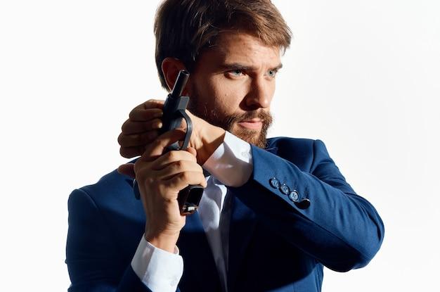 Mężczyzna w garniturze, trzymając broń detektywa przestępczości na białym tle. wysokiej jakości zdjęcie