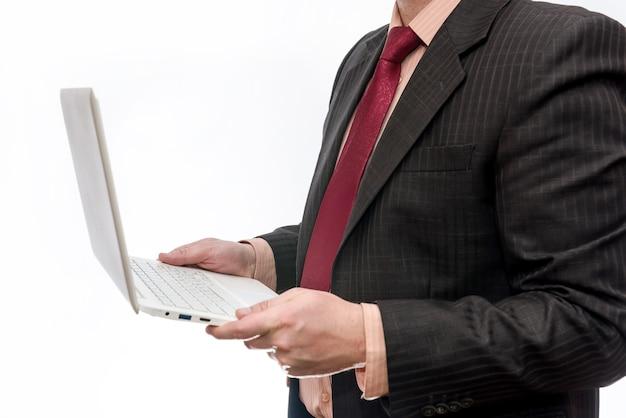 Mężczyzna w garniturze trzymając laptopa na białej powierzchni