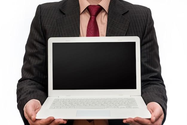 Mężczyzna w garniturze trzymając laptopa na białej ścianie
