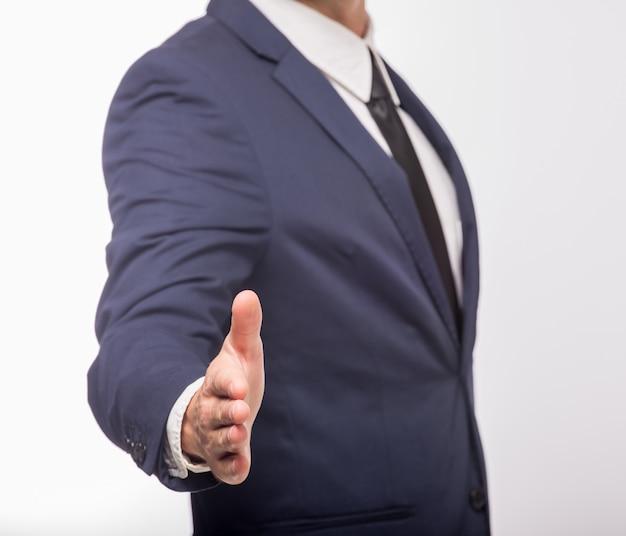 Mężczyzna w garniturze, trzymając otwartą dłoń, aby kogoś przywitać.