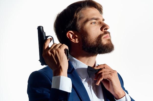 Mężczyzna w garniturze, trzymając pistolet styl życia gangstera mafia z bliska. wysokiej jakości zdjęcie