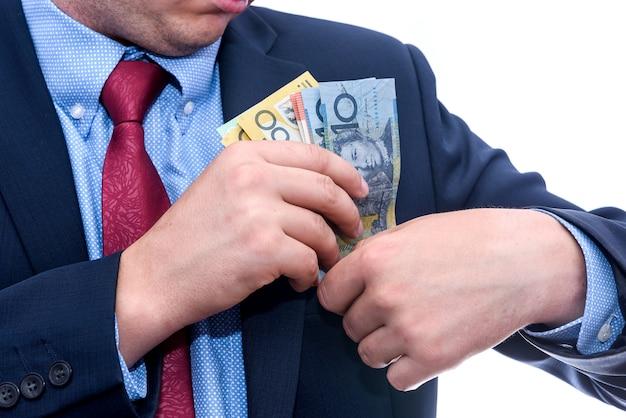 Mężczyzna w garniturze trzymający banknoty dolara australijskiego z bliska