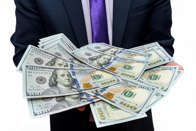 Mężczyzna w garniturze trzymający banknoty dolarowe z bliska