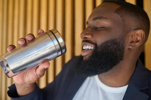 Mężczyzna w garniturze trzymający butelkę i wodę pitną