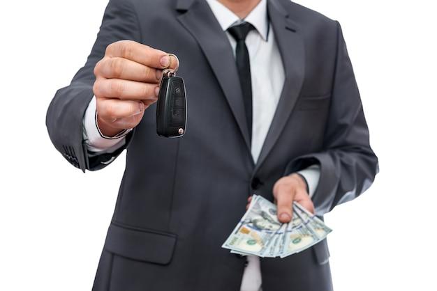 Mężczyzna w garniturze trzymający klucz od samochodu i dolarów