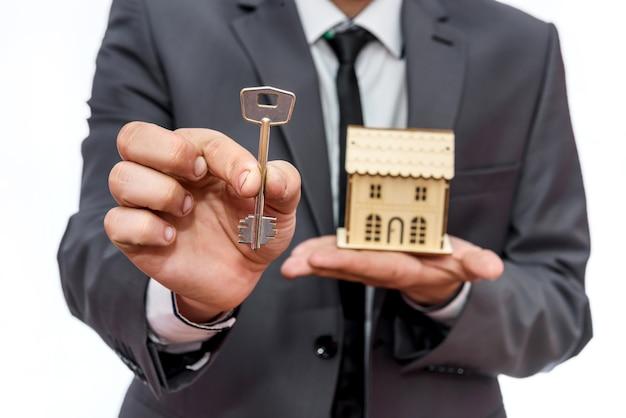 Mężczyzna w garniturze trzymający model domu i klucze