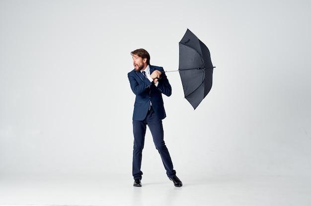 Mężczyzna w garniturze trzymający parasol nad głową, chroniący przed deszczem w eleganckim stylu studio
