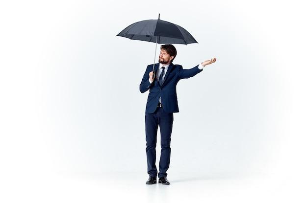 Mężczyzna w garniturze trzymający parasol nad głową specjalista od ochrony przed deszczem