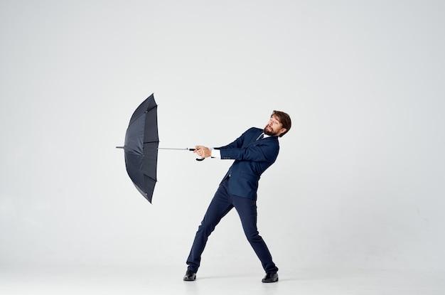 Mężczyzna W Garniturze Trzymający Parasol W Dłoniach Elegancki Styl Pogoda Deszcz Premium Zdjęcia